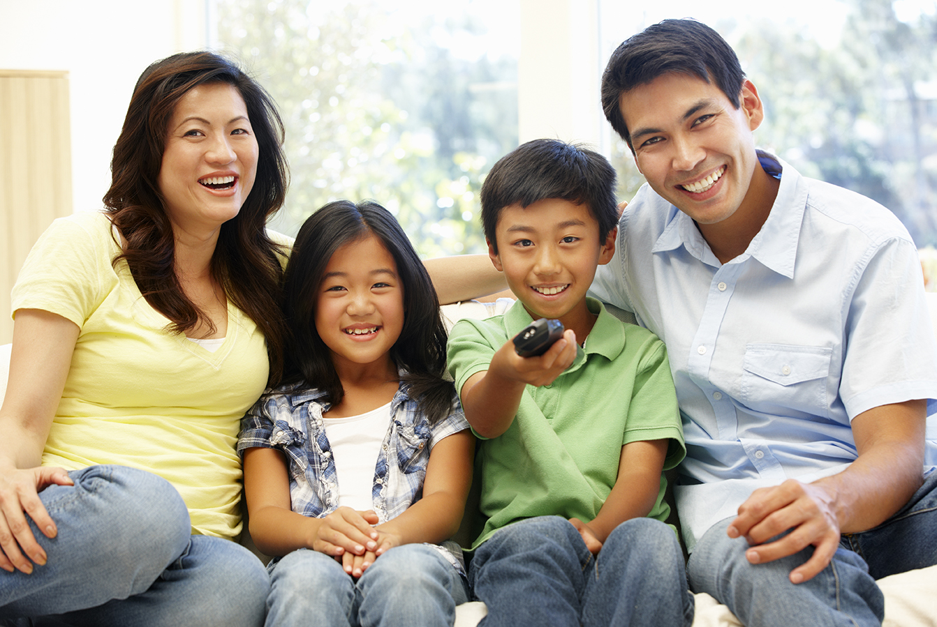 Image of family on couch with TV remote