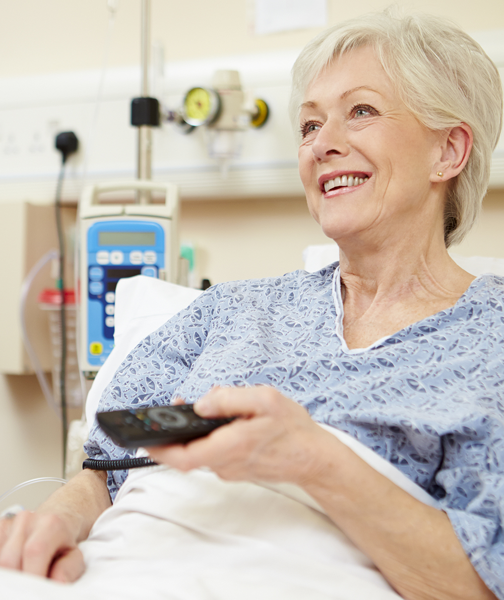 Image of a woman watching TV from her hospital bed.